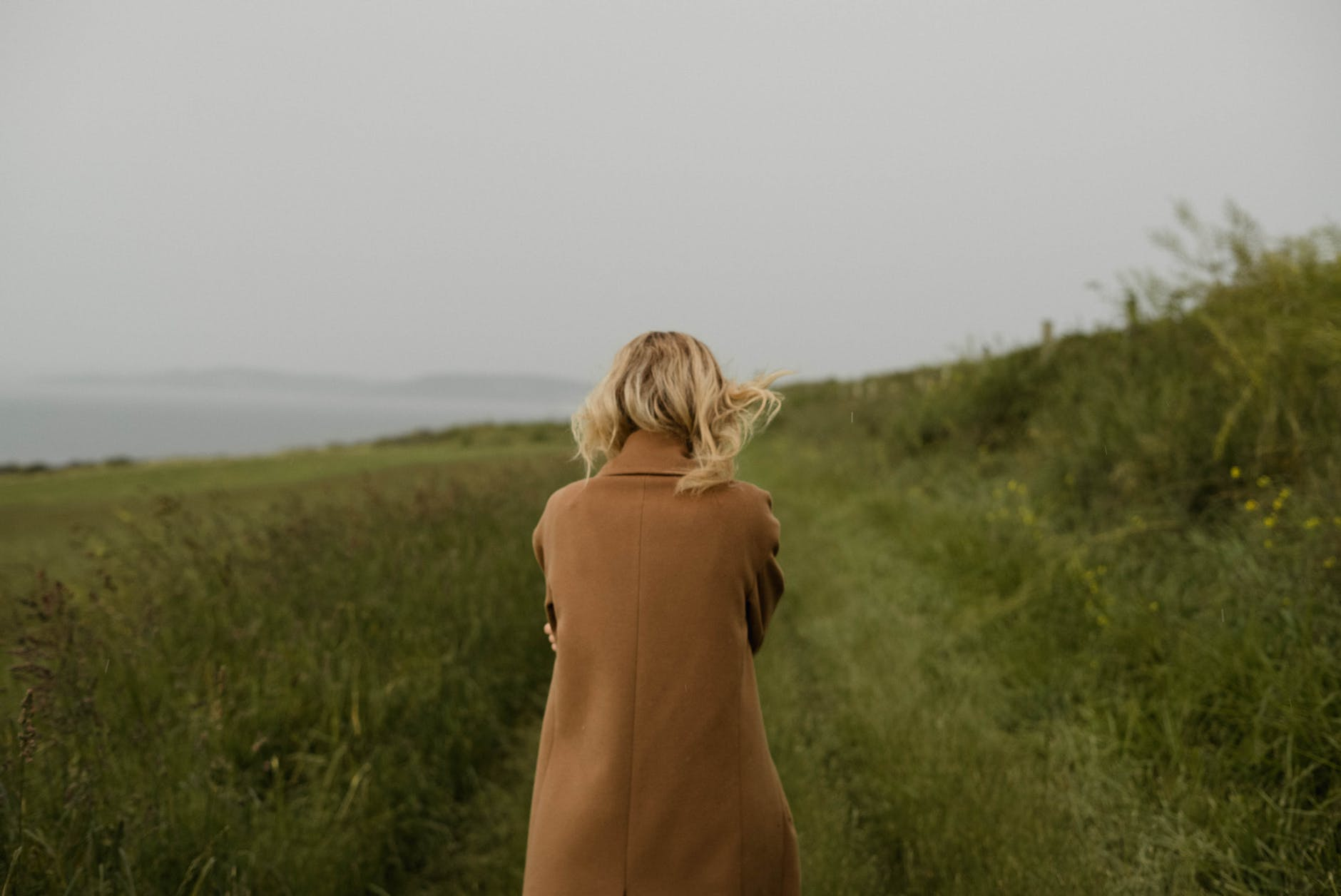 anonymous woman walking in cold field